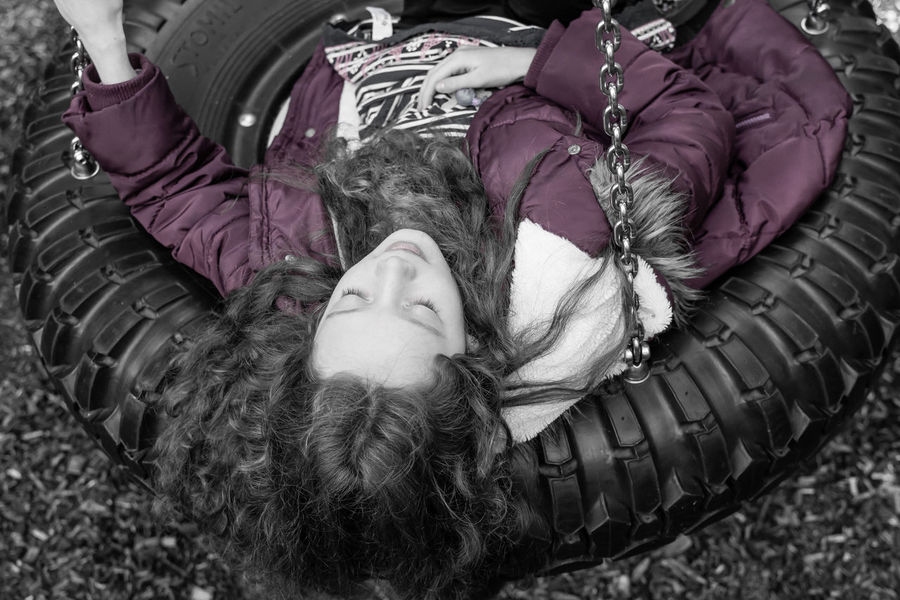 Child Childhood Day High Angle View Lying Down Lying On Back One Person One Woman Only One Young Woman Only Only Women Outdoors People Portrait Purple Real People S Tyre Swing Warm Clothing Young Adult Young Women