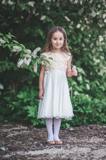 Portrait of a smiling girl standing against plants