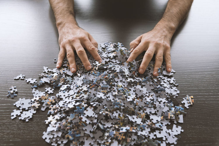 Overhead view of hands with jigsaw puzzle pieces on a tabletop. Mess Adult Adults Only Birds Eye View Close-up Confusing Day Frustration High Angle View Human Body Part Human Hand Indoors  Jigsaw Puzzle Large Group Of Objects Life In Pieces One Man Only One Person Only Men People Pieces Puzzle  Strategy Struggling Table