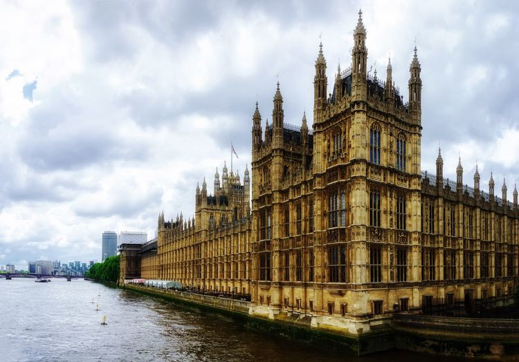 View of westminster building by river against sky in city