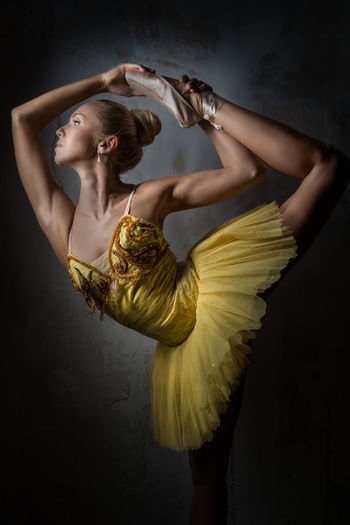 Beautiful ballerina dancing against wall in dark