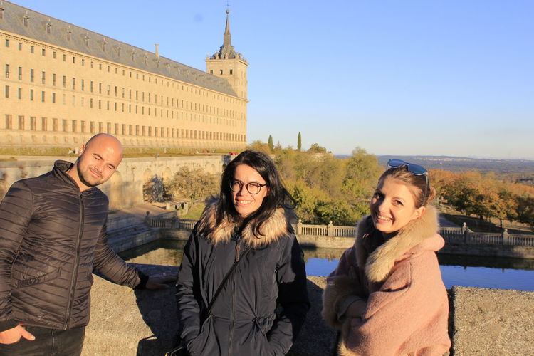 Portrait of smiling friends standing against historical palace