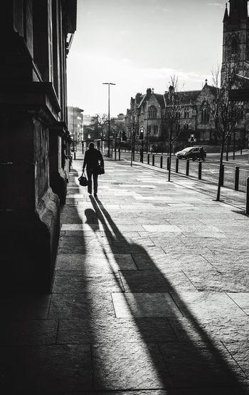 Silhouette man walking on footpath by buildings