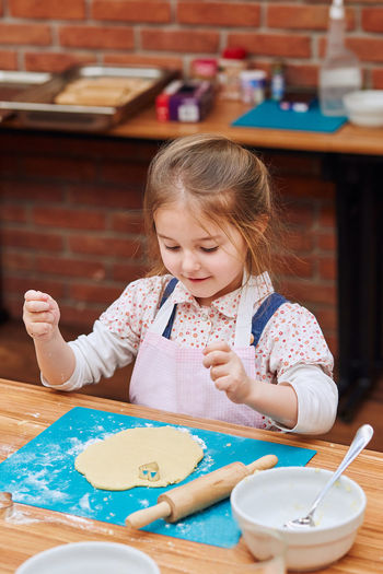 High angle view of cute girl making cookies on table at home
