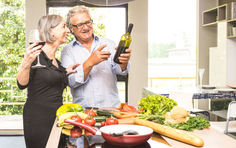 Man With Woman Holding Wine Bottle In Kitchen At Home