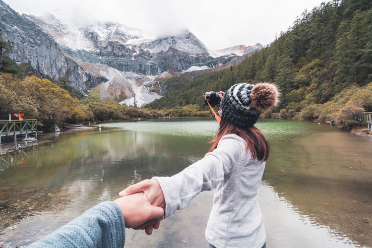 Cropped hand of man holding woman hand at lake against mountains