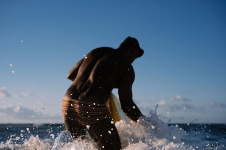 Man playing in sea against clear blue sky