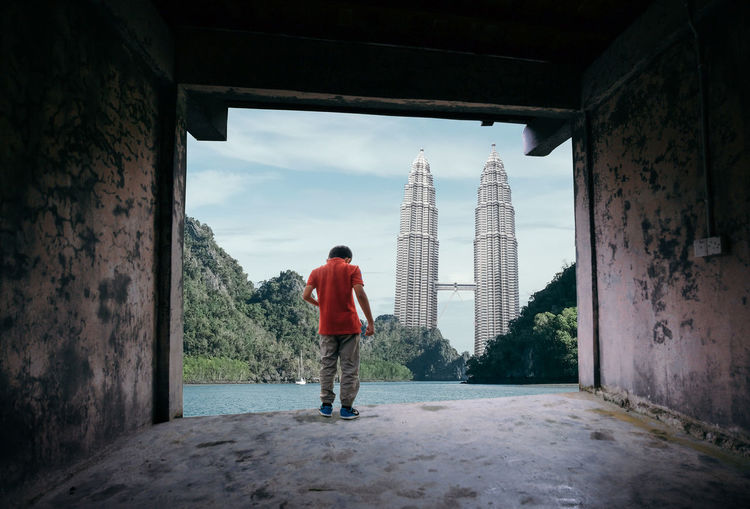 Rear view of boy standing by river with petronas towers in background