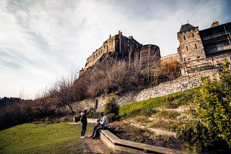 Friends in park with edinburgh castle in background against cloudy sky