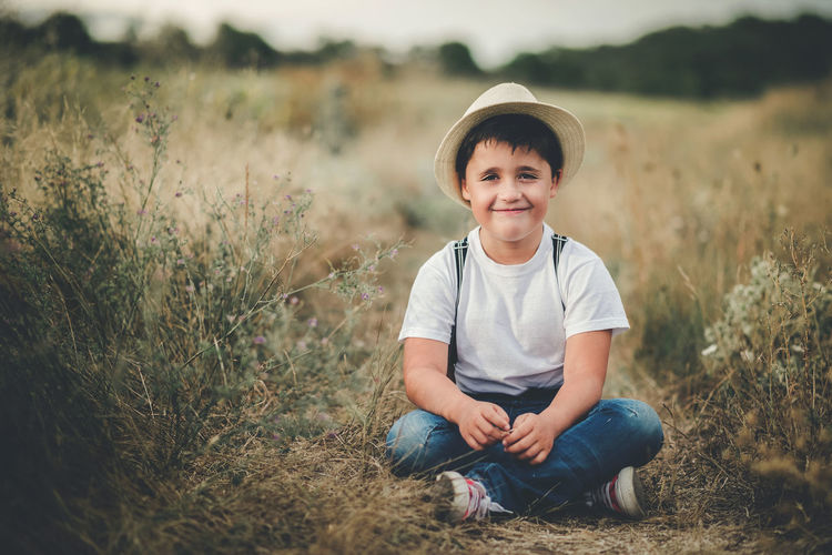 Portrait of smiling boy sitting on land
