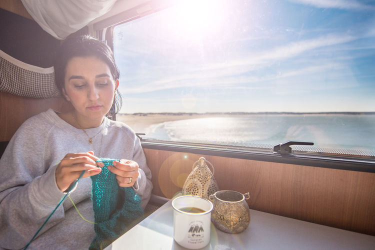 Woman Knitting Fabric While Having Coffee In Train