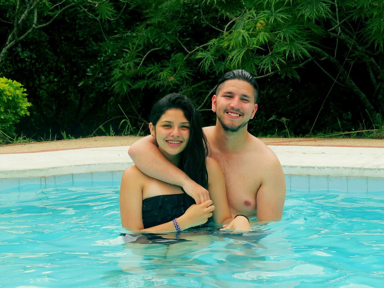 swimming pool, smiling, water, happiness, two people, looking at camera, leisure activity, togetherness, real people, portrait, cheerful, toothy smile, lifestyles, love, young men, young adult, young women, mid adult men, front view, bonding, fun, outdoors, shirtless, day, enjoyment, boys, vacations, nature, people