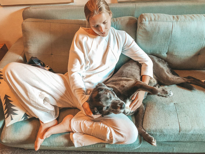 Woman with dog relaxing on sofa at home