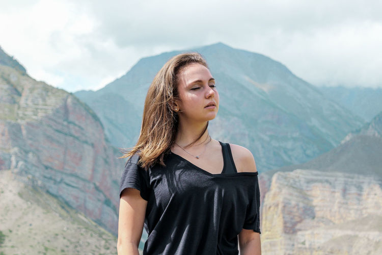 Beautiful young woman standing against mountain range