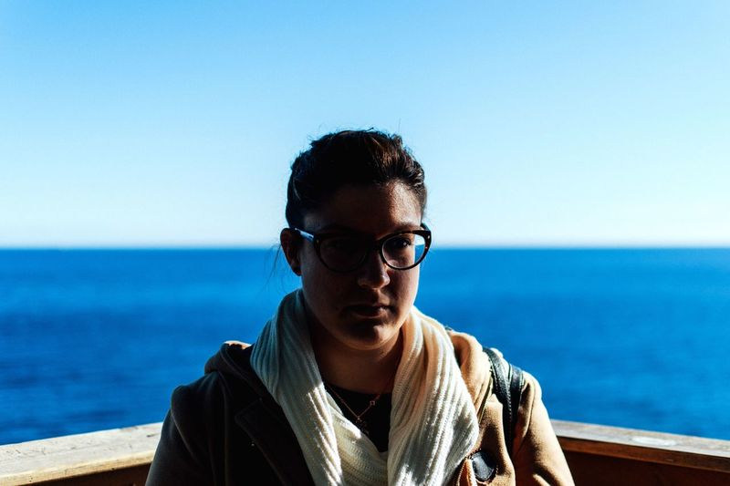 Close-Up Of Serious Woman Wearing Eyeglasses Standing Against Sea