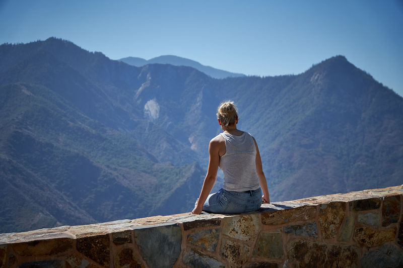 Rear view of woman sitting on retaining wall against mountain