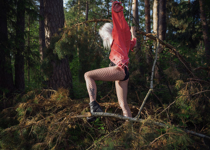 Side view of woman wearing lingerie standing in forest
