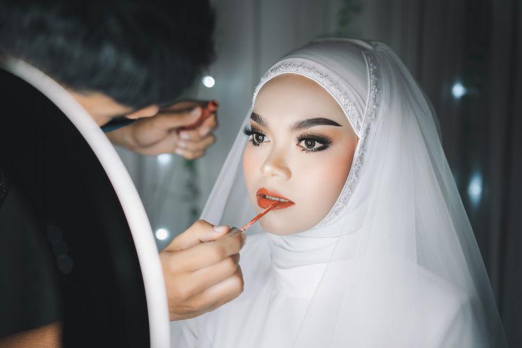 Beautiful bride wearing make-up