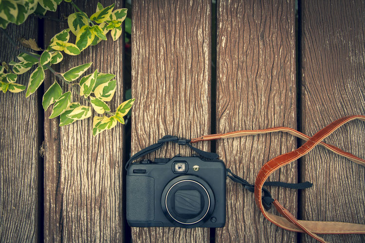 Compact camera on wooden background vintage color tone Brown Close-up Day Directly Above Electrical Equipment Leaf Nature No People Plant Plant Part Retro Styled Technology Wood - Material