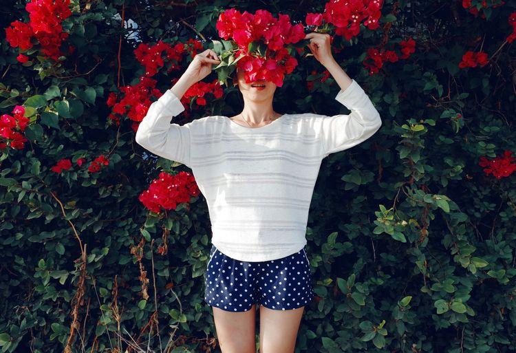 Beautiful woman standing by flower tree in garden