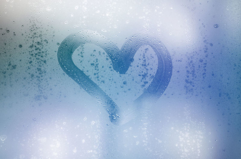 Close-up of heart shape on wet glass