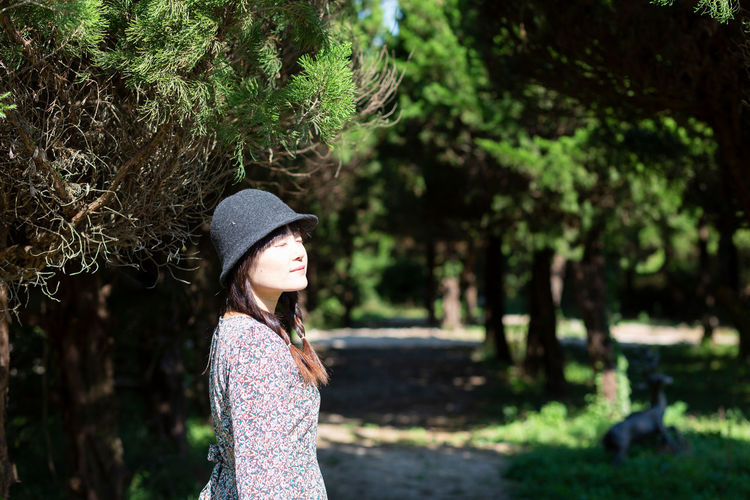 Woman wearing hat standing against trees