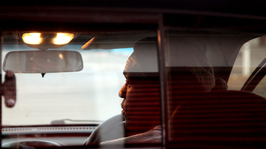 Rear view of man traveling in car seen through rear windshield