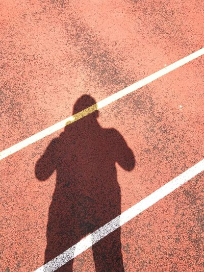 Shadow Of Man On Sports Track