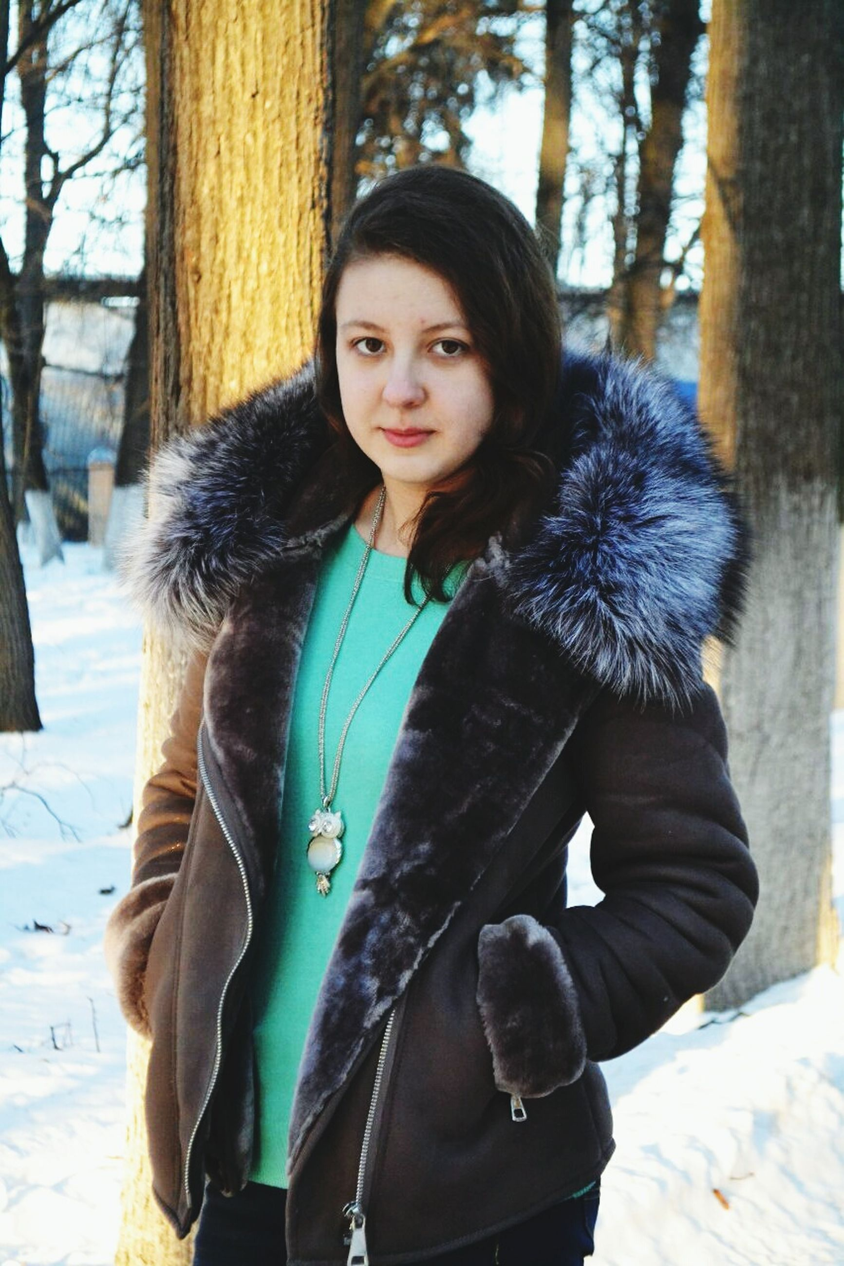 young adult, long hair, young women, lifestyles, person, casual clothing, leisure activity, front view, portrait, looking at camera, three quarter length, standing, smiling, tree, waist up, focus on foreground, jacket