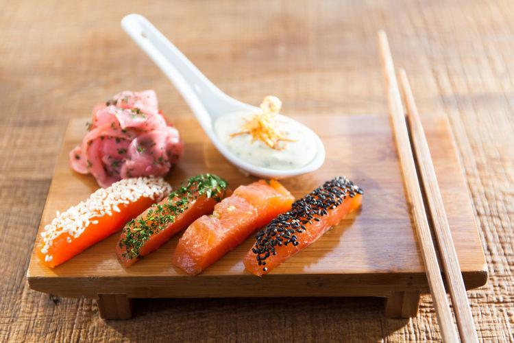 High angle view of sashimi with chopsticks on table