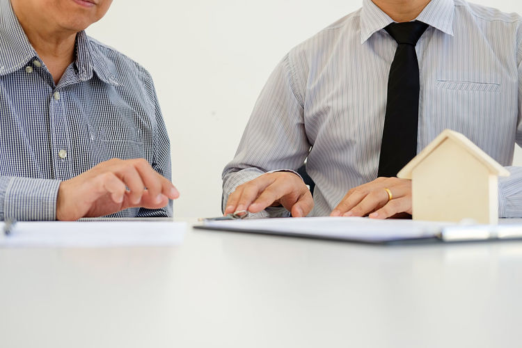 Midsection Of Real Estate Agent Sitting With Client At Office