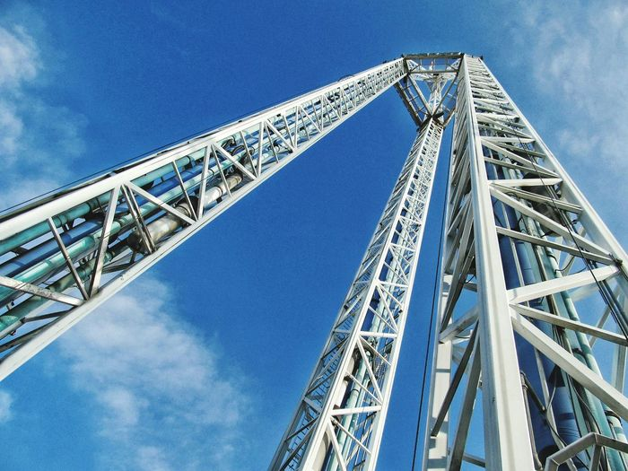 Low angle view of free falling ride against blue sky on sunny day