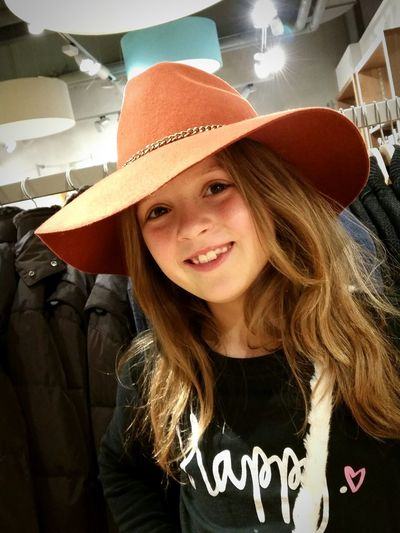 Portrait Of Smiling Cute Girl Wearing Hat At Store