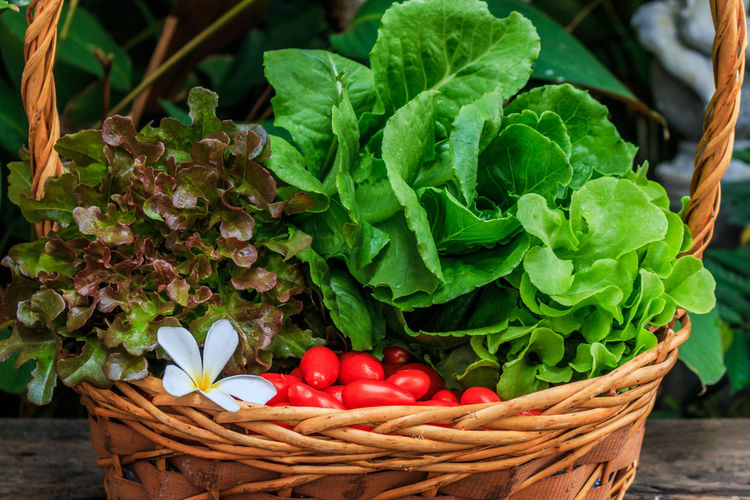 Fresh vegetables in wicker basket on table