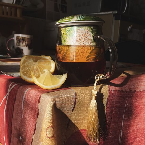 Close-up of half lemon by teapot on table