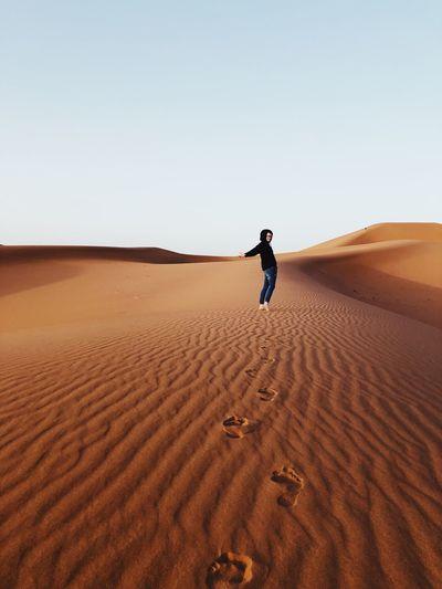 Full length of woman standing on sand dune in desert against sky