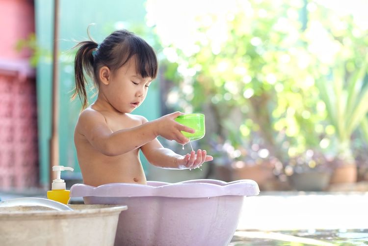 Little girl playing water in the plastic basin happily in the garden. Tub Playing Water Bath Bathtub Basin Girl Child Kids Cute Childhood Child One Person Innocence Nature Sitting Offspring Water Focus On Foreground Looking Young Cute Baby Emotion Happiness Holding Refreshment Outdoors Hairstyle