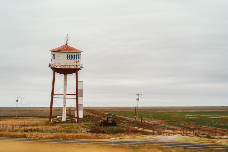 Water tower on field by building against sky