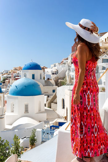 Attractive traveler woman in red dress enjoys the view to the village of Oia, Santorini, Greece, during summer time Architecture Built Structure Women Building Exterior Day Real People Sunlight Lifestyles Fashion Young Adult Hairstyle Outdoors White Color Clothing Tourist Travel Destinations Traveler Dress Santorini Oia Greece Island Church Village Tourist Attraction