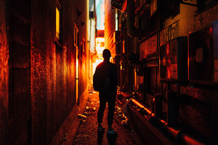 Rear view of man walking on illuminated alley amidst buildings in city