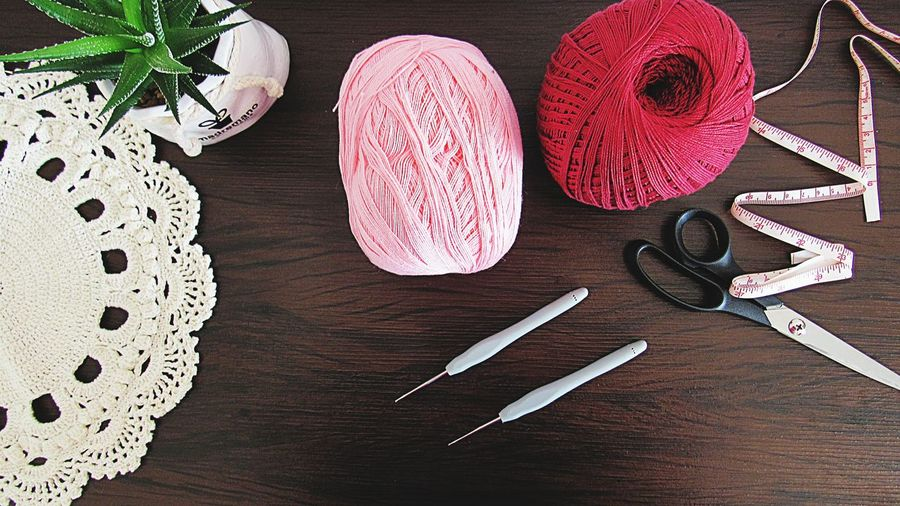 Directly above shot of wool ball with crochet and scissor over table