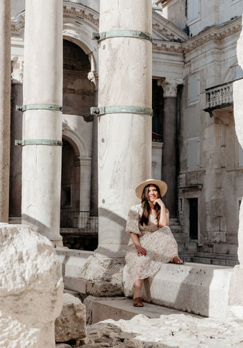 Full length of woman sitting at historic building