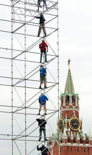 Men standing on metal built structure against spasskaya tower