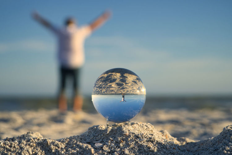Man enjoys freedom on the beach at sanibel island, taken through a glass ball