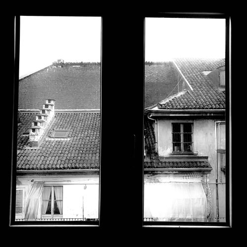 Buildings against clear sky seen through glass window