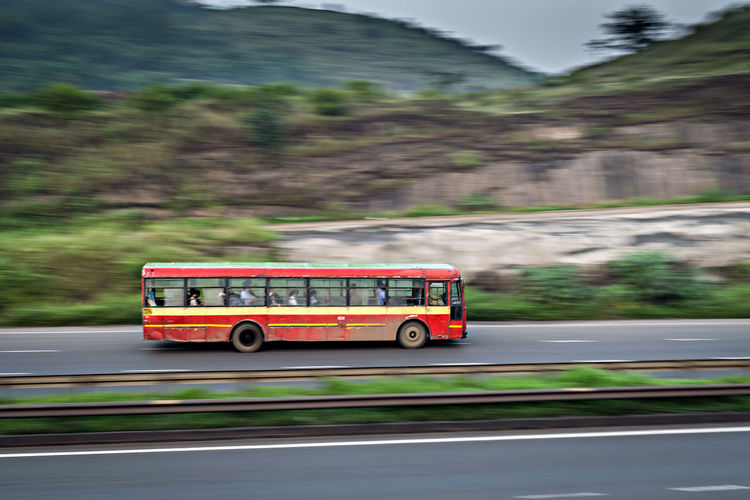 Bus moving on road against mountain