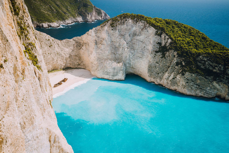 Navagio beach or Shipwreck bay with turquoise water and pebble white beach. Famous landmark location. overhead landscape of Zakynthos island, Greece Water Sea Scenics - Nature Rock Rock - Object Beauty In Nature Nature Land No People Solid Day Rock Formation Tranquil Scene Mountain Blue Tranquility Travel Destinations Outdoors Turquoise Colored Bay Lagoon Navagio Beach Unique Places Greece Miracle