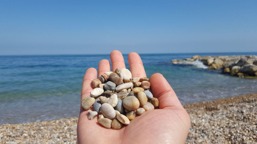 Close-up of hand holding stones at beach