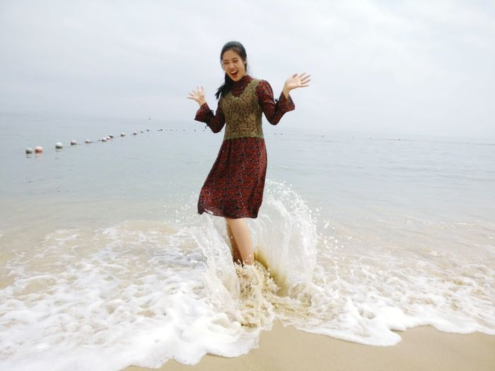 Full Length Of Young Woman Standing In Sea