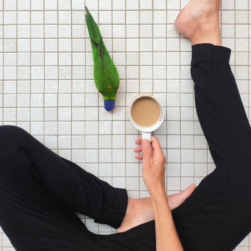 Low section of man holding coffee cup on floor
